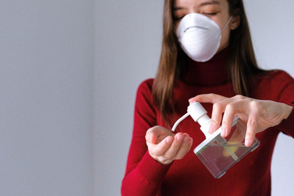 woman-applying-hand-sanitizer-3987146